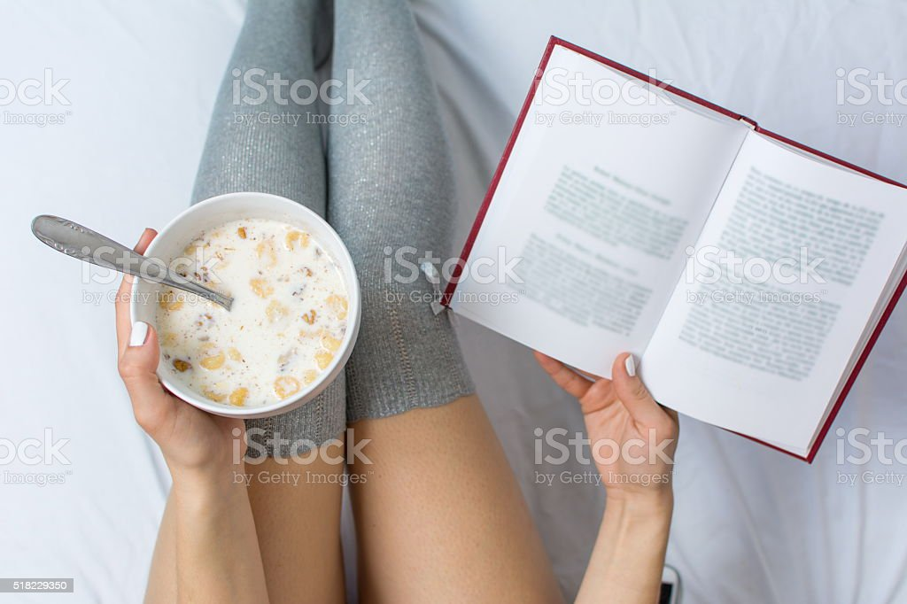 Woman eating cereals and reading in bed stock photo