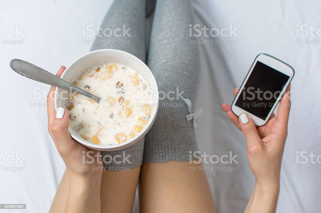 Woman eating cereals and texting in bed stock photo