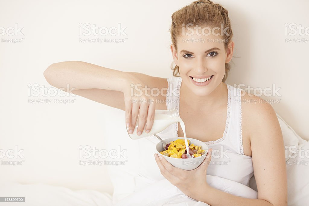 Woman eating cereals in bed. royalty-free stock photo