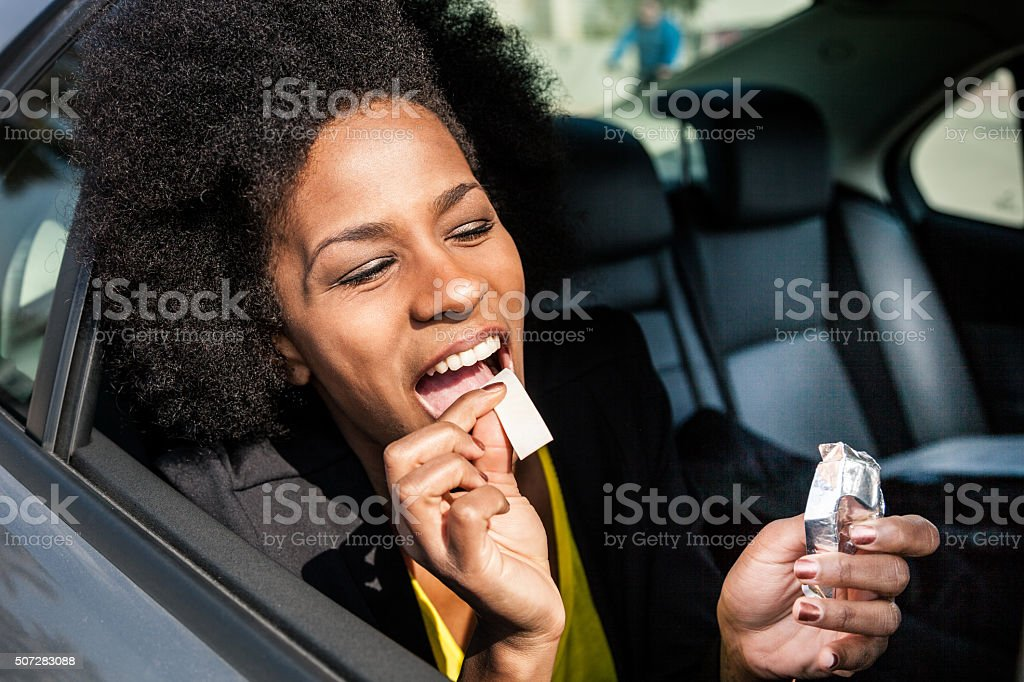 Woman eating chewing gum on a road trip stock photo