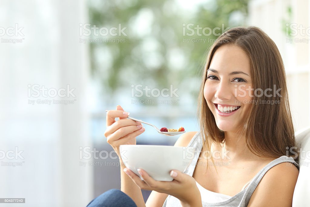 Casual happy woman dieting and eating cornflakes sitting on a couch...