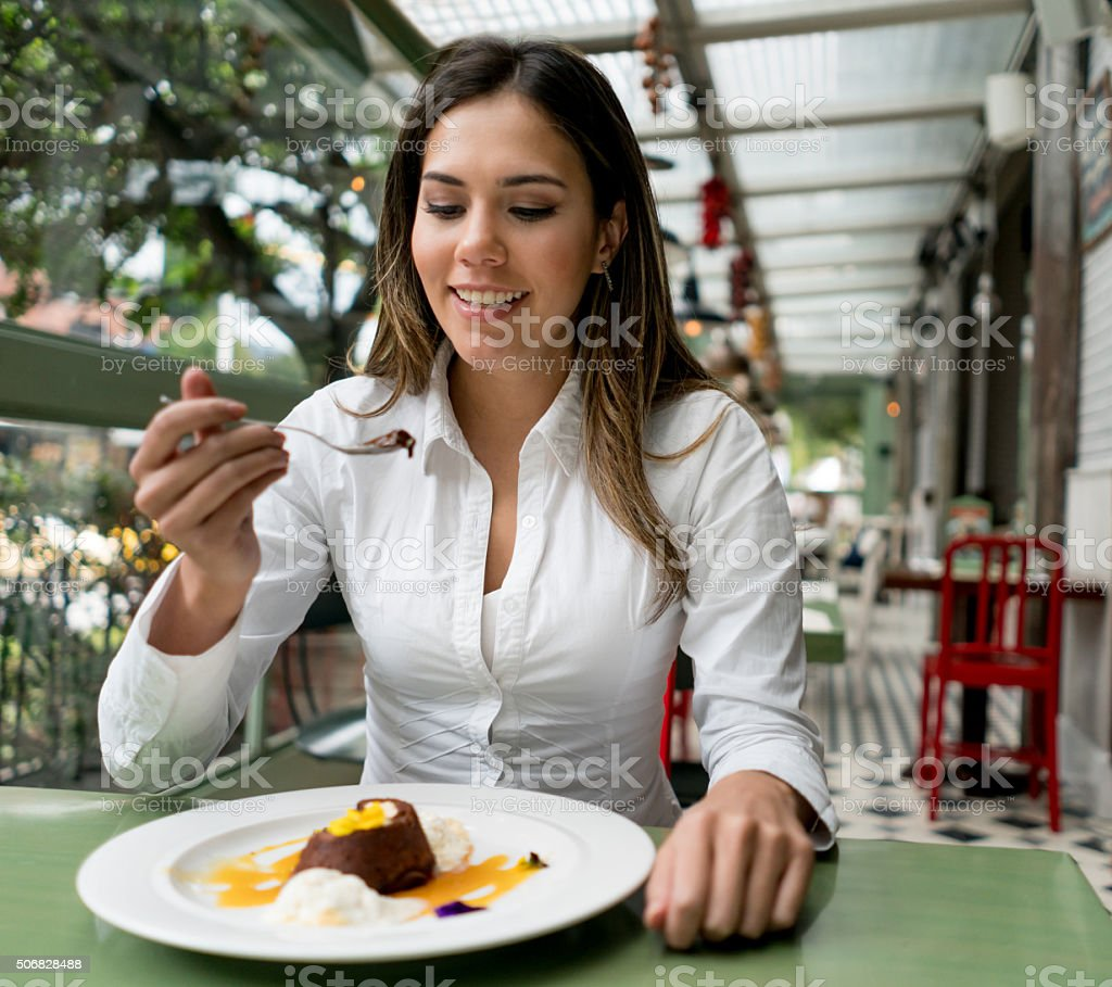Woman eating dessert at a coffee shop stock photo