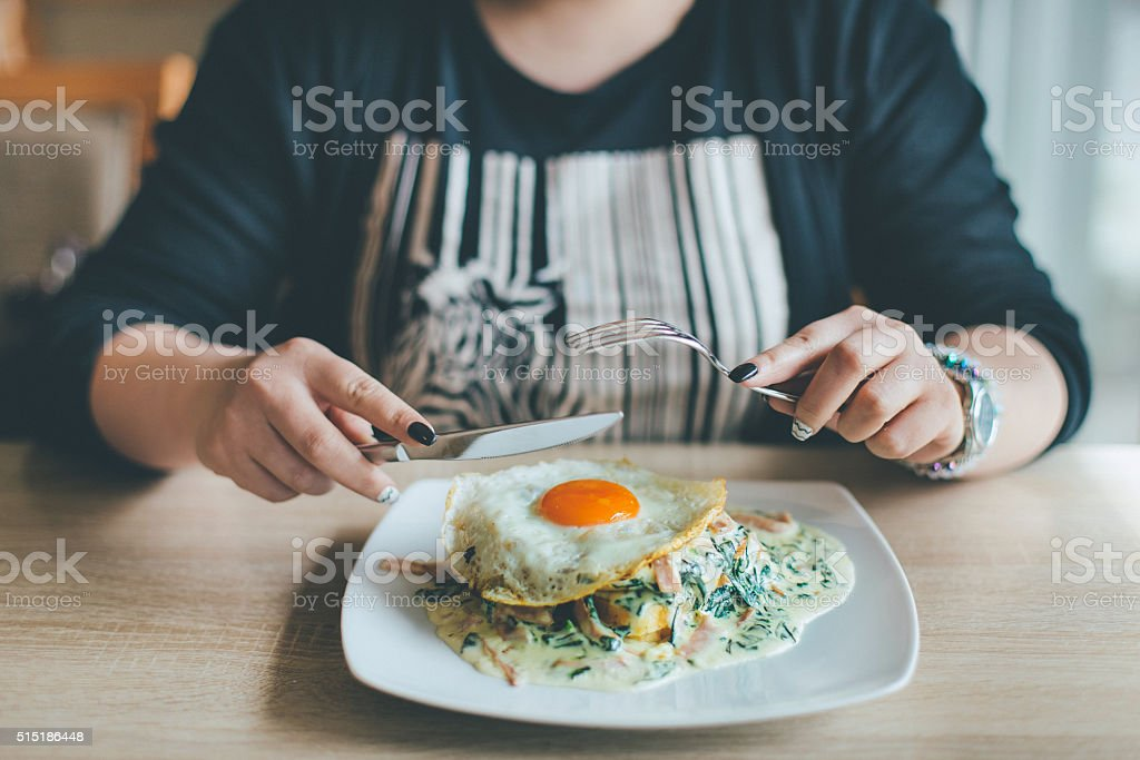 Woman eating English breakfast stock photo