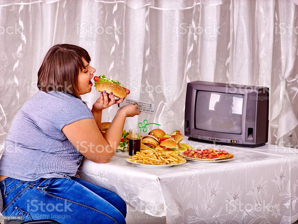 Woman eating fast food and watching TV stock photo