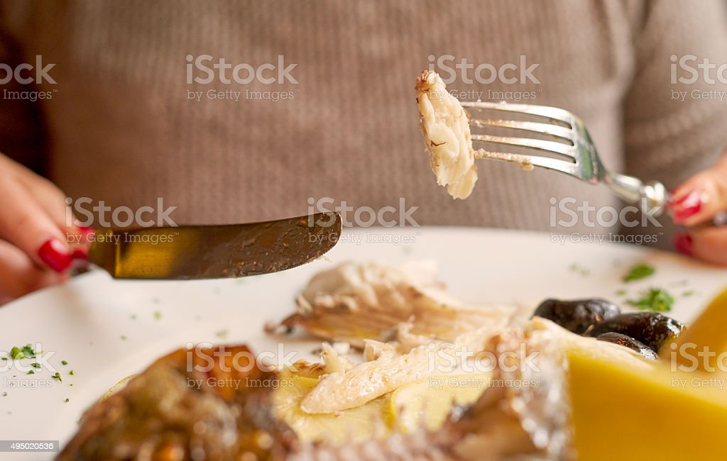 woman eating fish stock photo