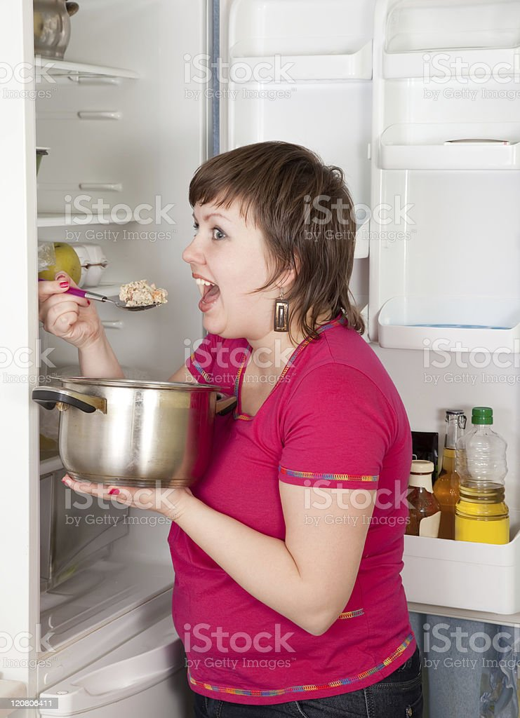woman eating  from pan near  fridge royalty-free stock photo