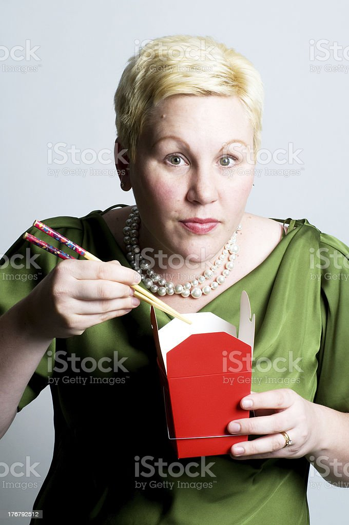 Woman Eating from Take Out Container stock photo