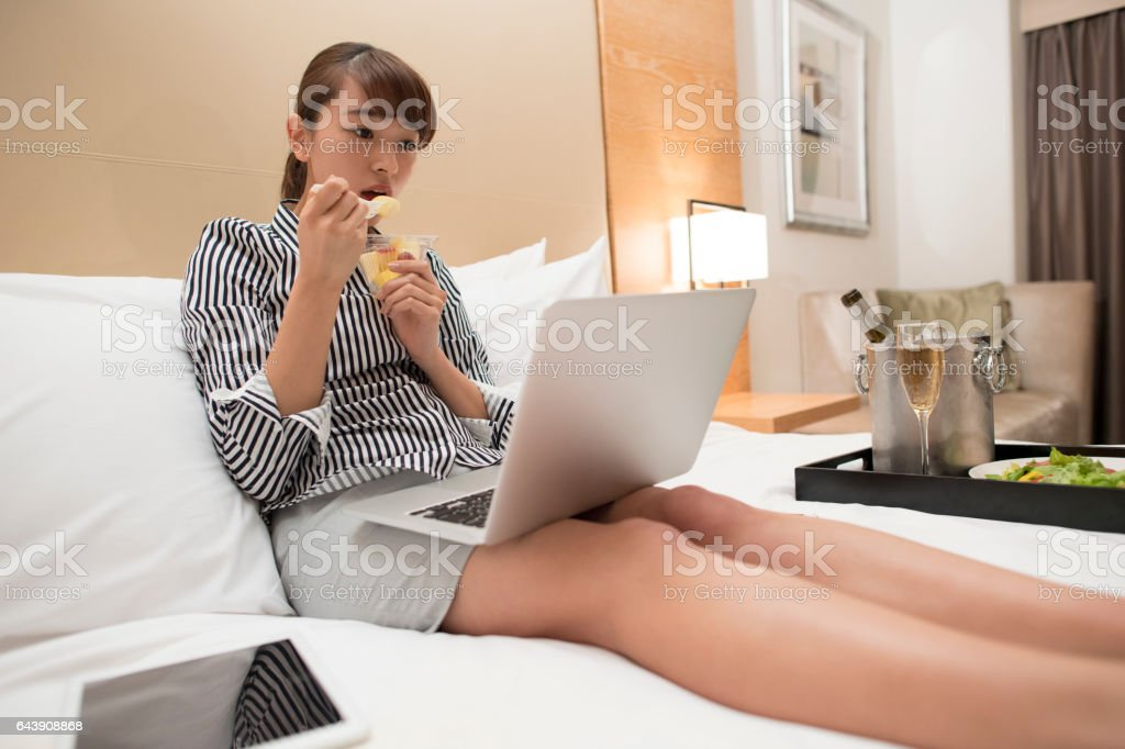 A woman eating fruit while watching a computer. stock photo