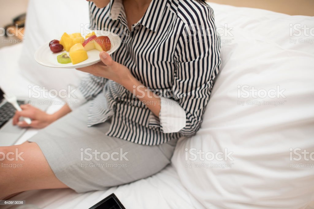 A woman eating fruit while watching a computer stock photo