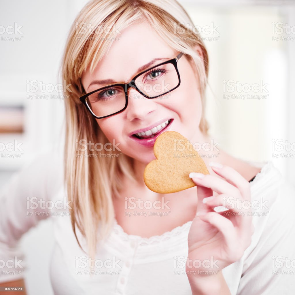 woman eating gingerbread cookie royalty-free stock photo