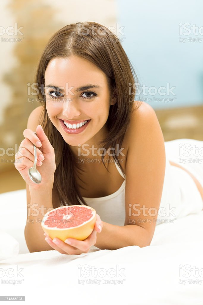 Woman eating grapefruit on bed, at home royalty-free stock photo