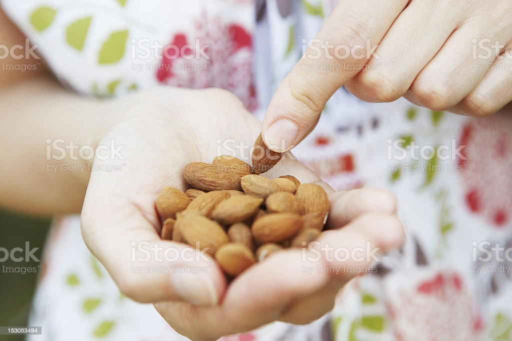 Woman Eating Handful Of Almonds stock photo