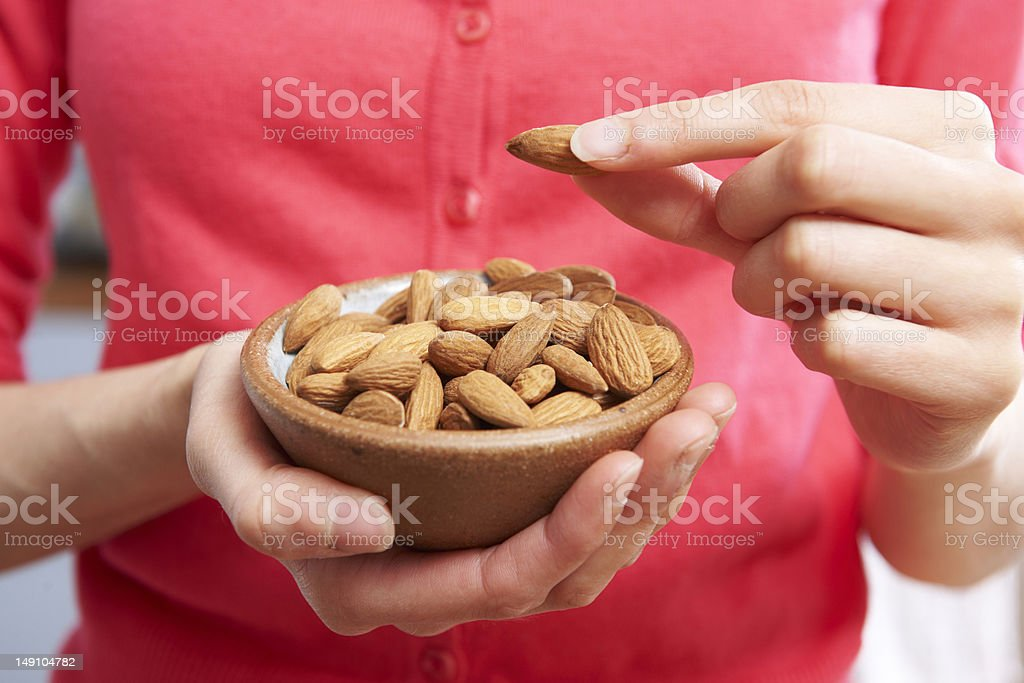 Woman Eating Healthy Snack Of Almonds stock photo