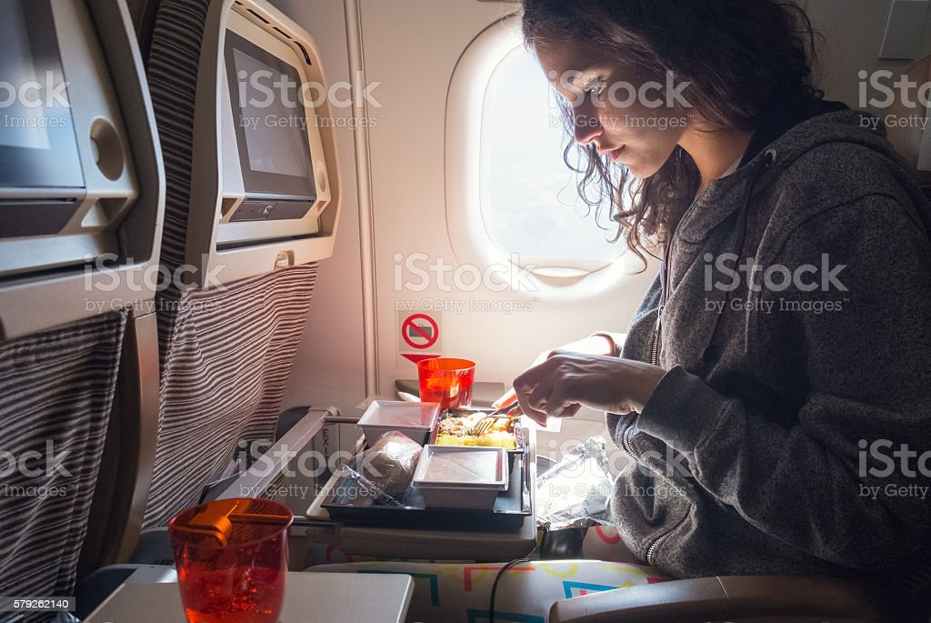 Woman eating lunch in airplane stock photo