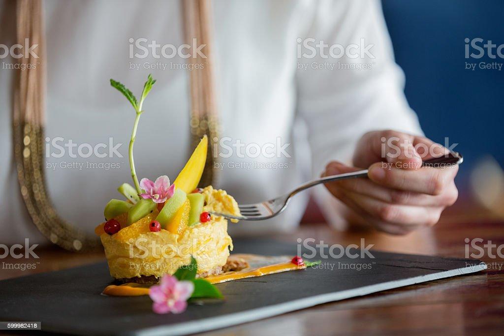 Woman eating mango mousse cake stock photo
