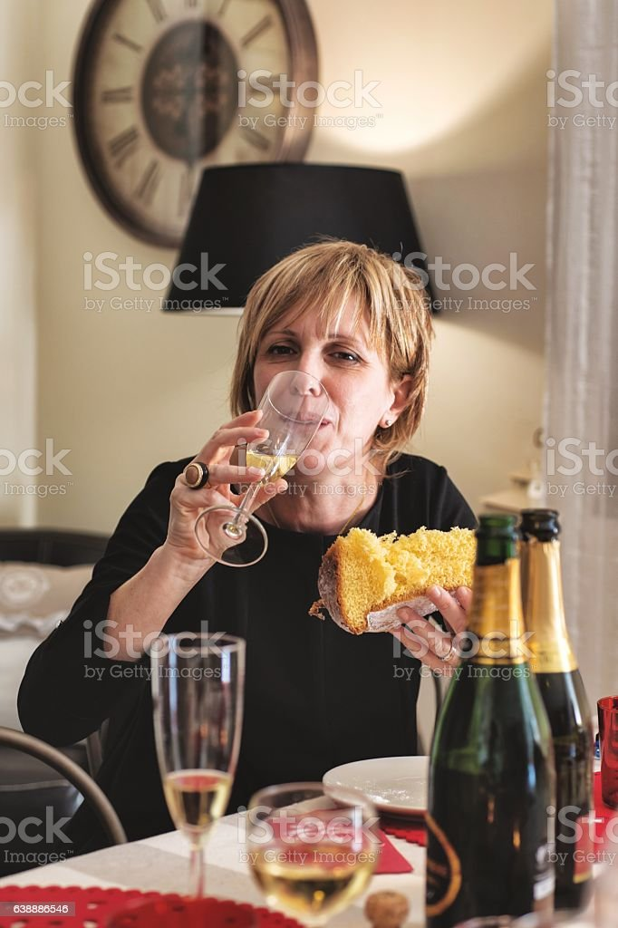 Woman Eating Pandoro During New Year's Eve Party in Italy stock photo
