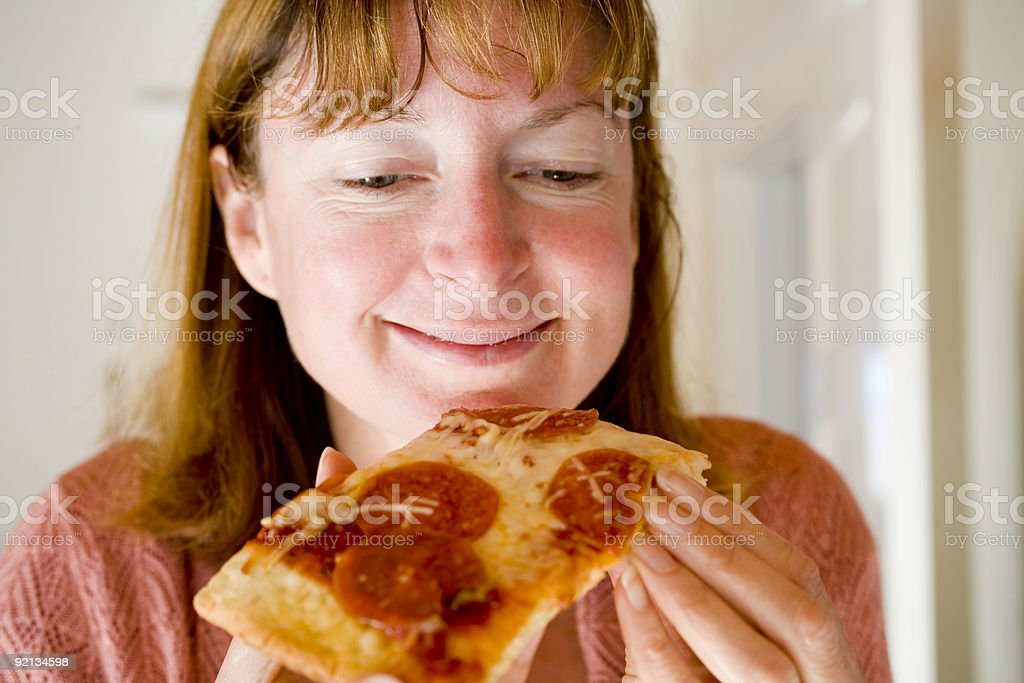 Woman Eating Pepperoni Pizza royalty-free stock photo