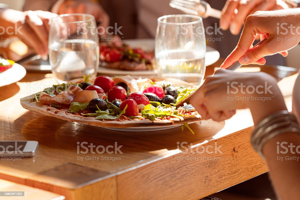 Woman eating pizza in the restaurant stock photo