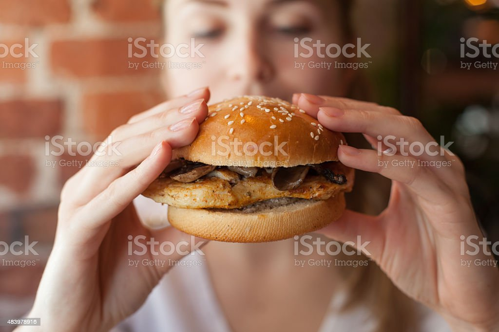 Woman eating some burger stock photo