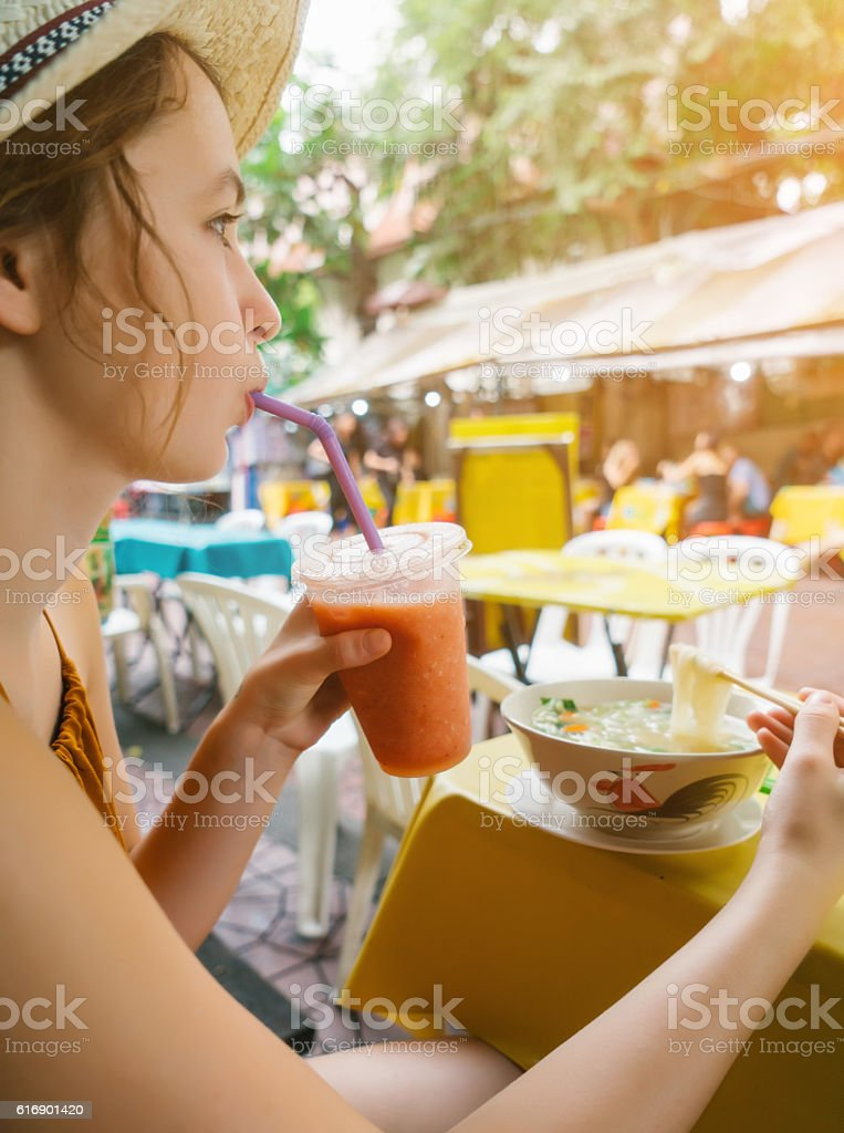 Woman eating soup and drinking juice stock photo