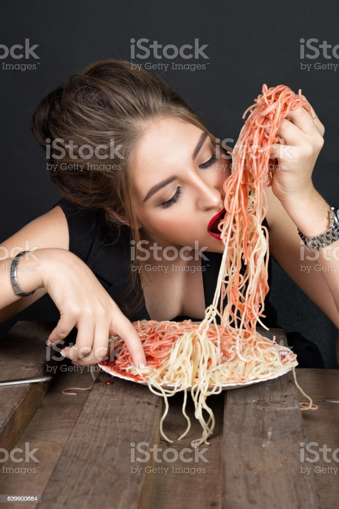Woman eating spaghetti at wooden table stock photo