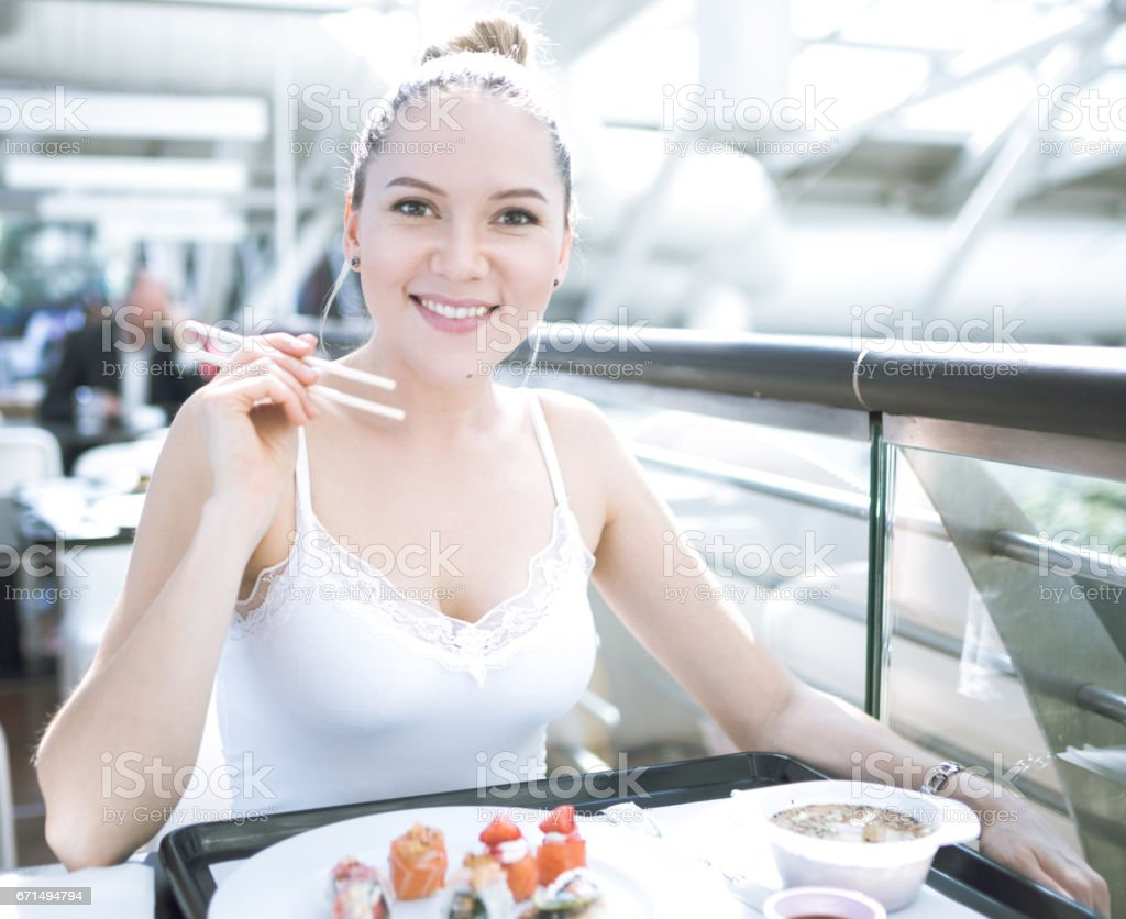 Woman eating sushi on the food court stock photo