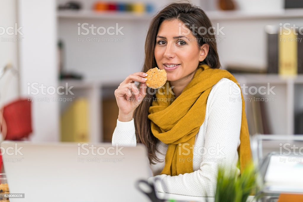 Woman eating tasty cookie stock photo