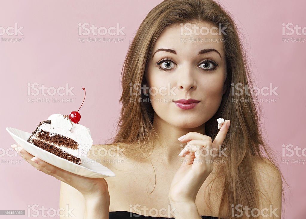 Woman eating the cream from a cream cake stock photo
