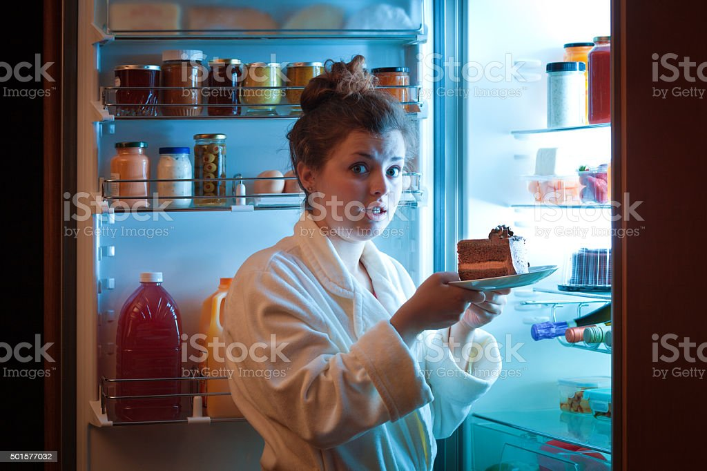 Woman Eating Unhealthy Chocolate Cake in Front of Open Refrigerator stock photo