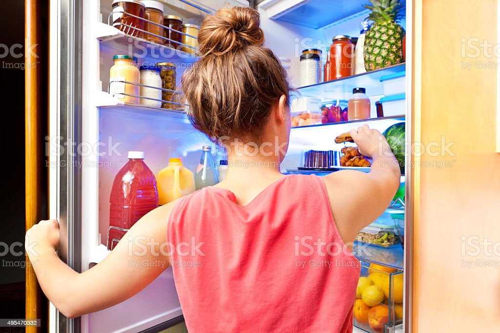 Woman Eating Unhealthy Fried Chicken in Front of Open Refrigerator stock photo