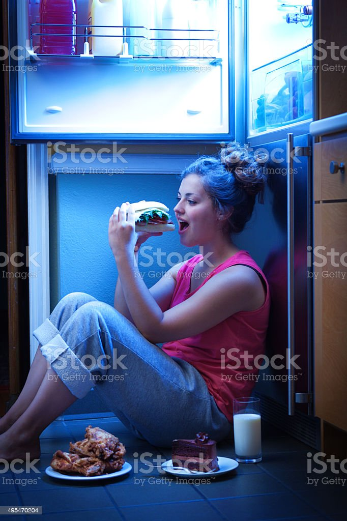 Woman Eating Unhealthy Midnight Snack late Night Under Open Refrigerator stock photo
