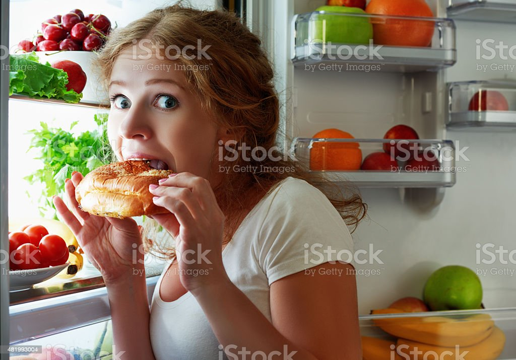 Woman eats night stole the refrigerator stock photo