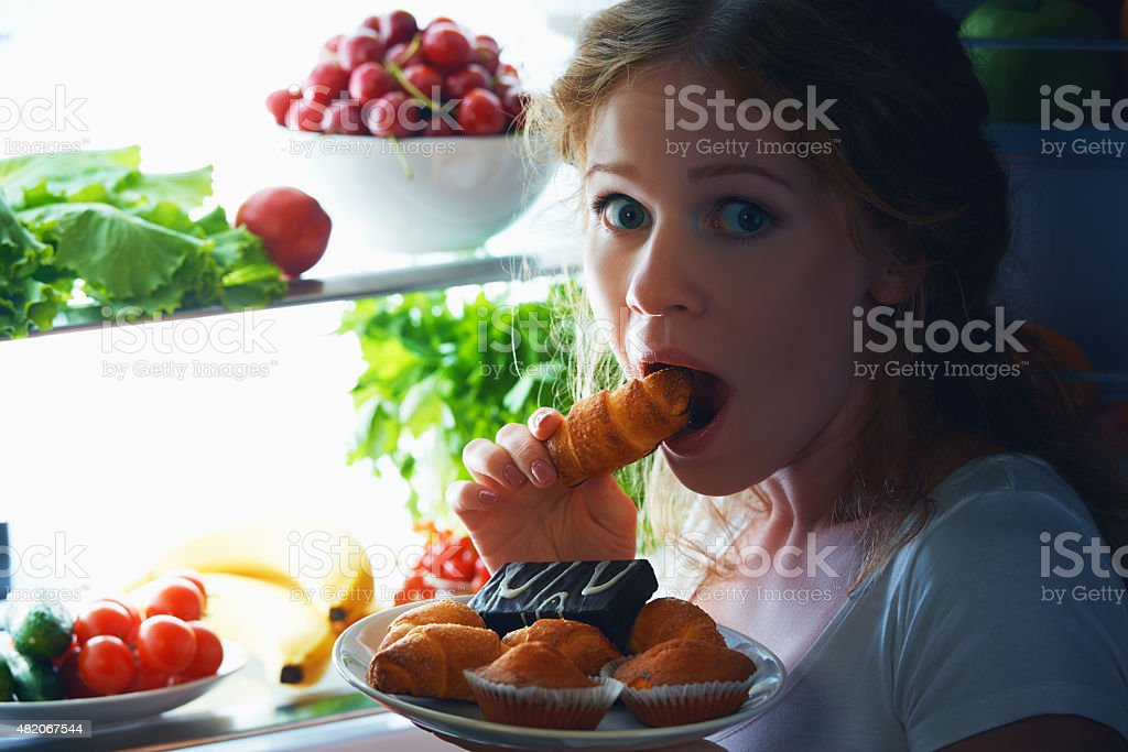 Woman eats night stole the refrigerator stock photo