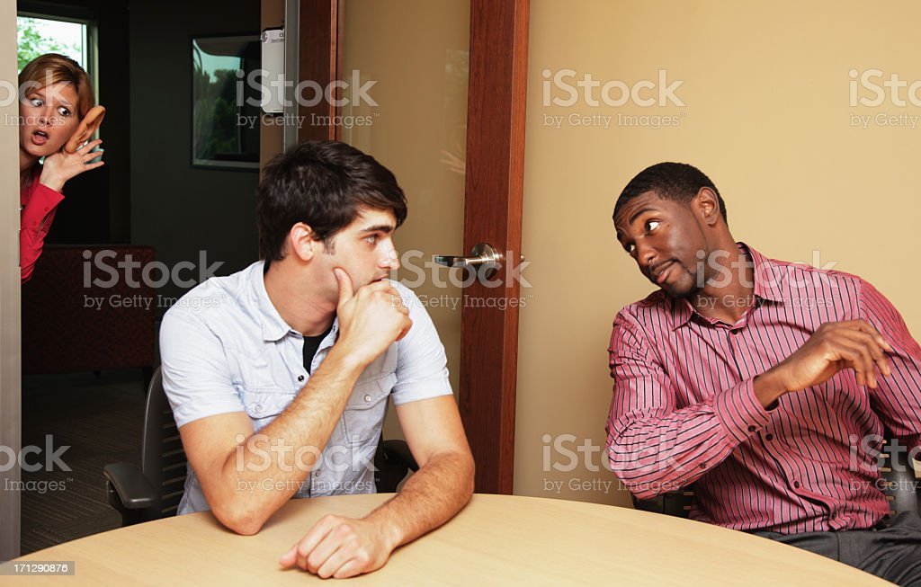 Woman Eavesdropping on Two Guys Conversation stock photo