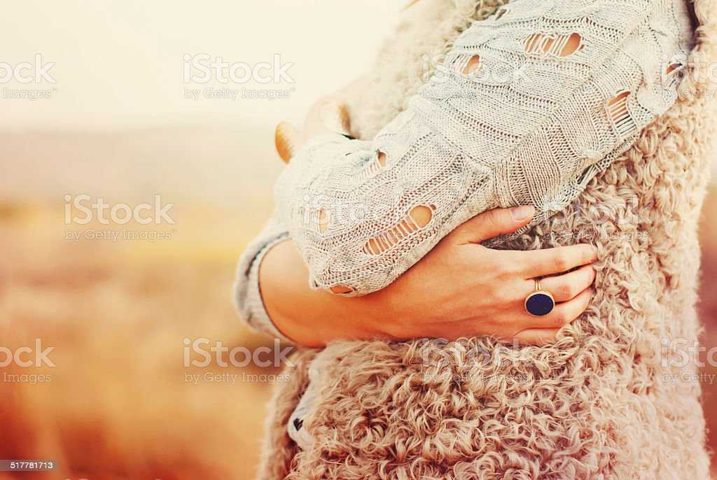 Woman Embraces Herself Hands, Ring in the finger stock photo