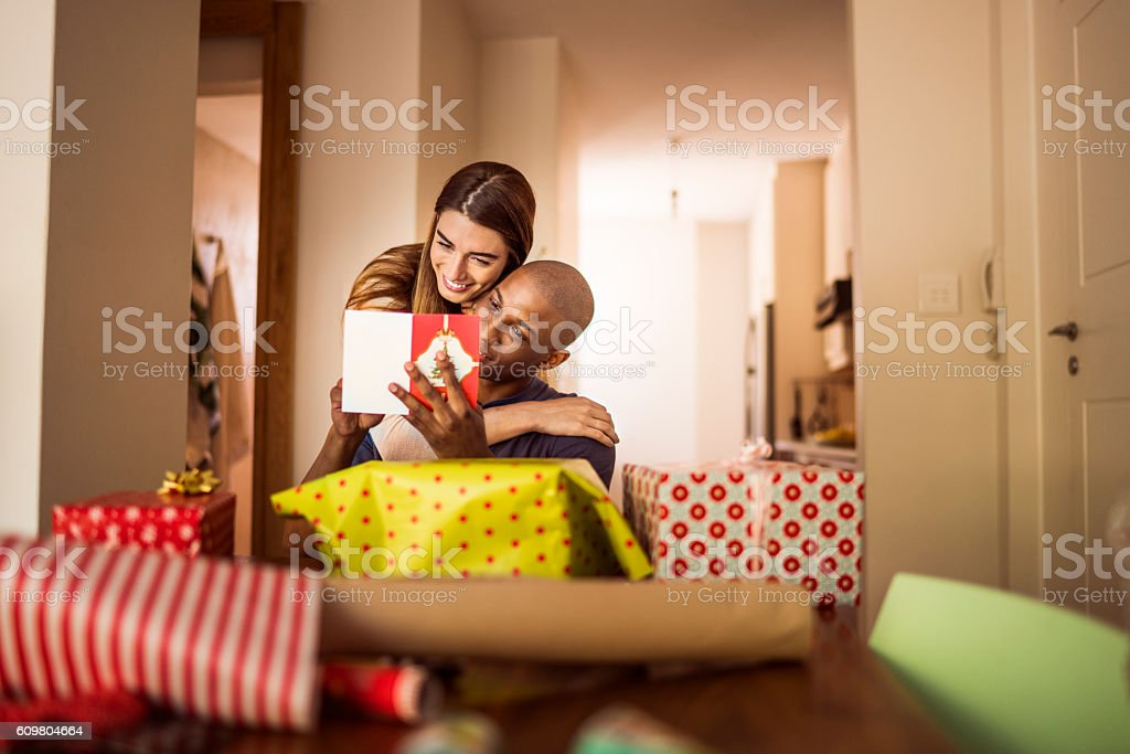 Woman embracing boyfriend while reading card stock photo