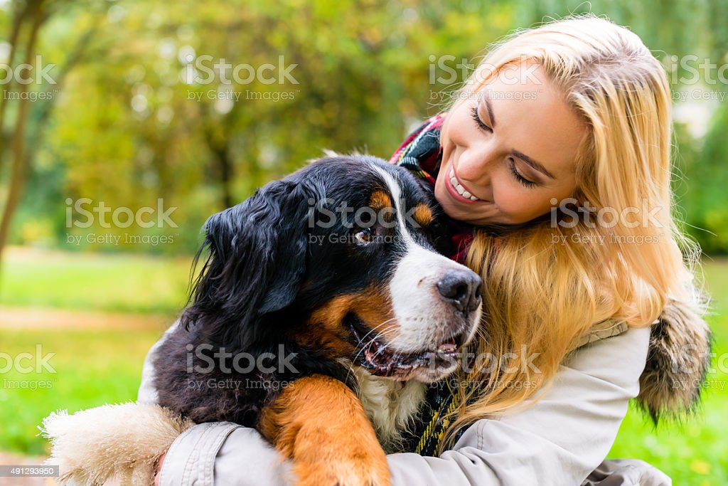 Woman embracing her dog in autumn park stock photo