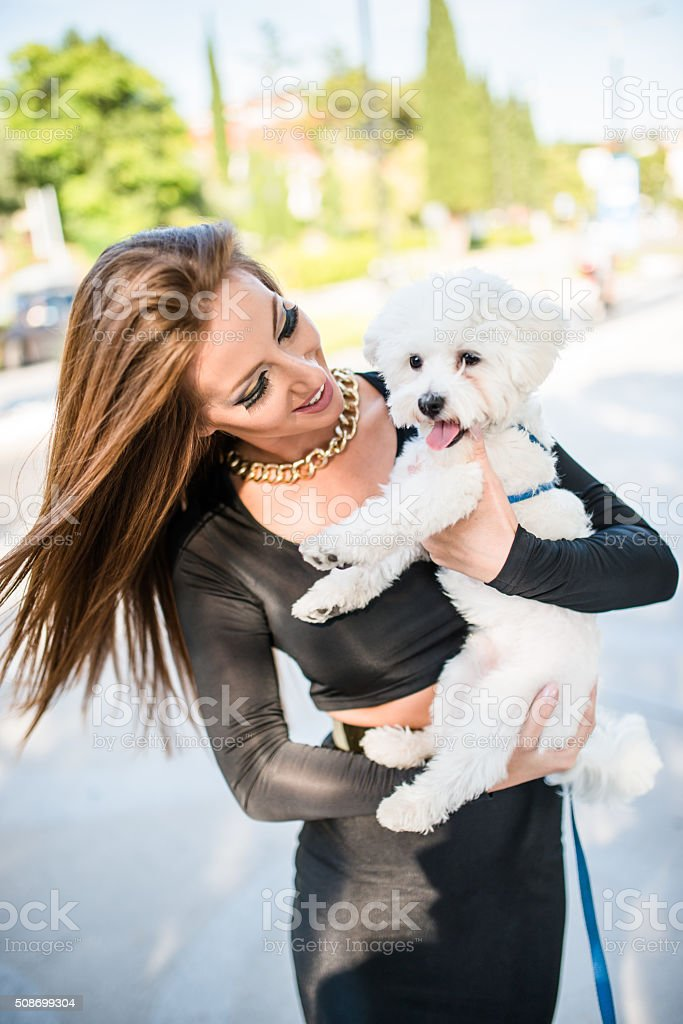 woman embracing her dog on the street stock photo