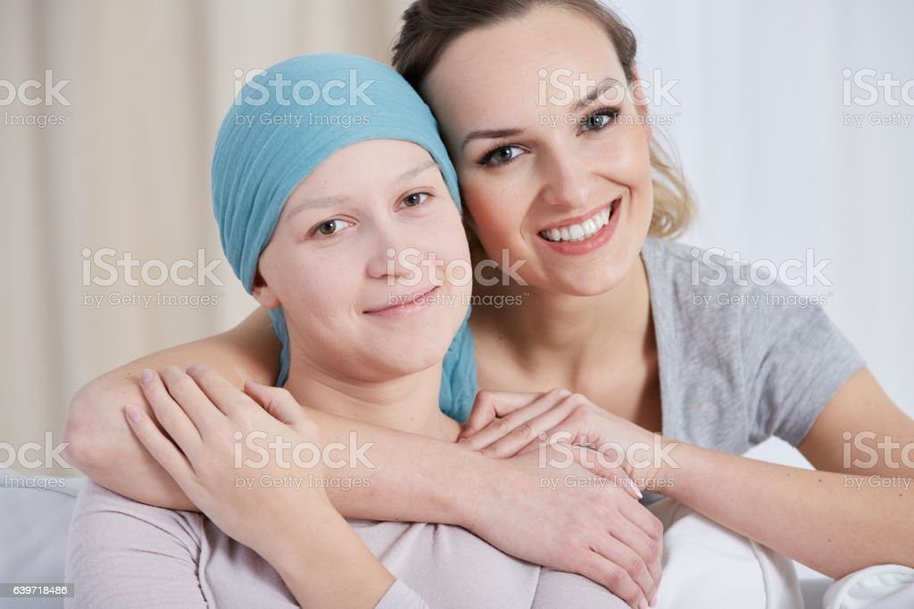 Woman embracing her ill sister stock photo