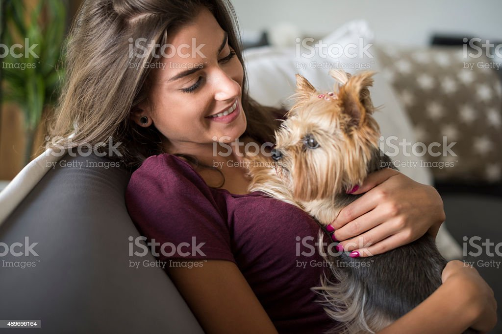 Woman embracing her little puppy stock photo