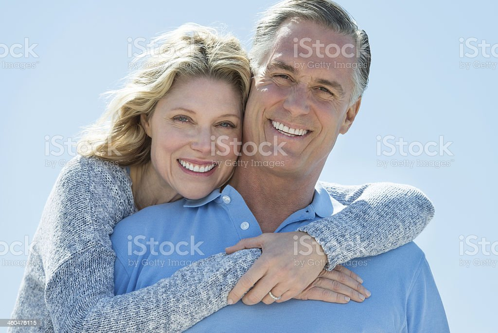 Woman embracing man from behind under clear sky stock photo
