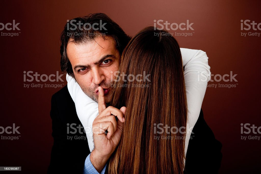 Woman embracing man making a shushing gesture stock photo
