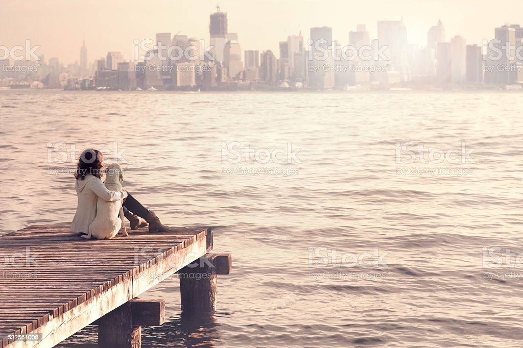 woman embracing sweetly her dog while looking NewYork city stock photo