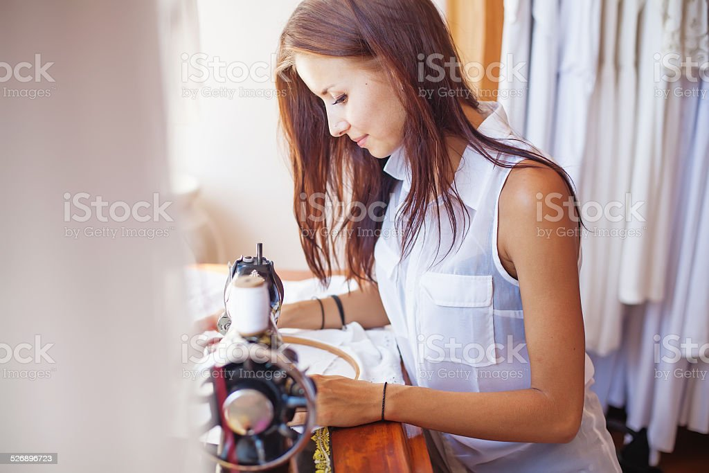 Woman embroidering a whte dress stock photo