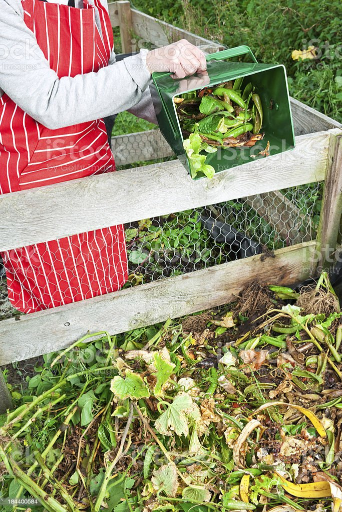 Woman emptying vegetable scraps in compost heap stock photo