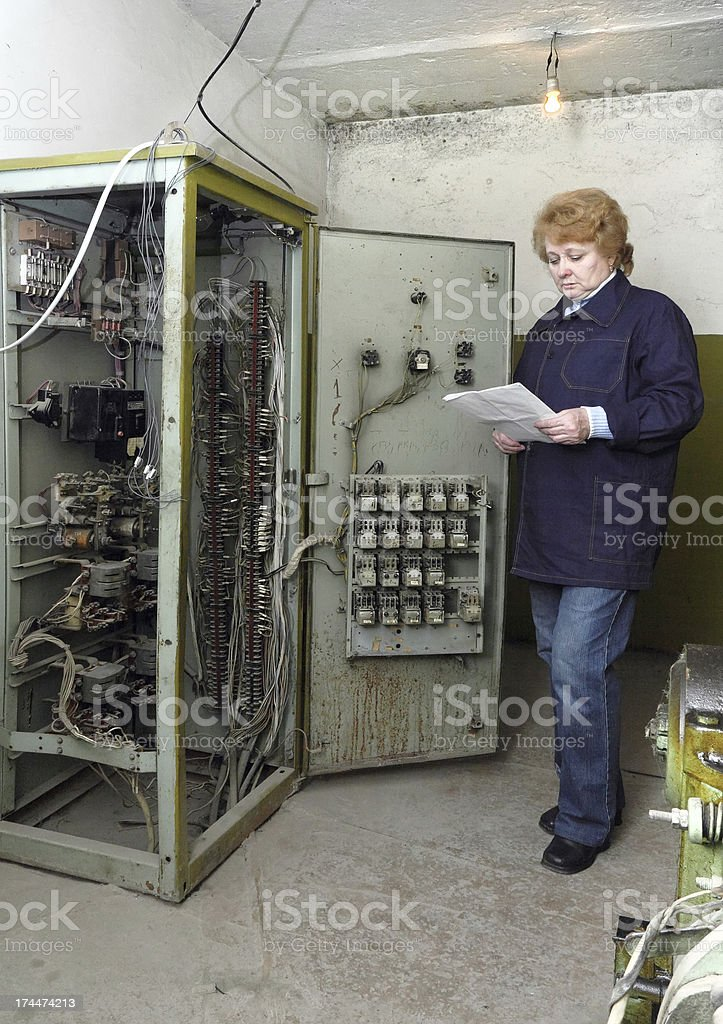Woman engineer in machine room (elevator) royalty-free stock photo