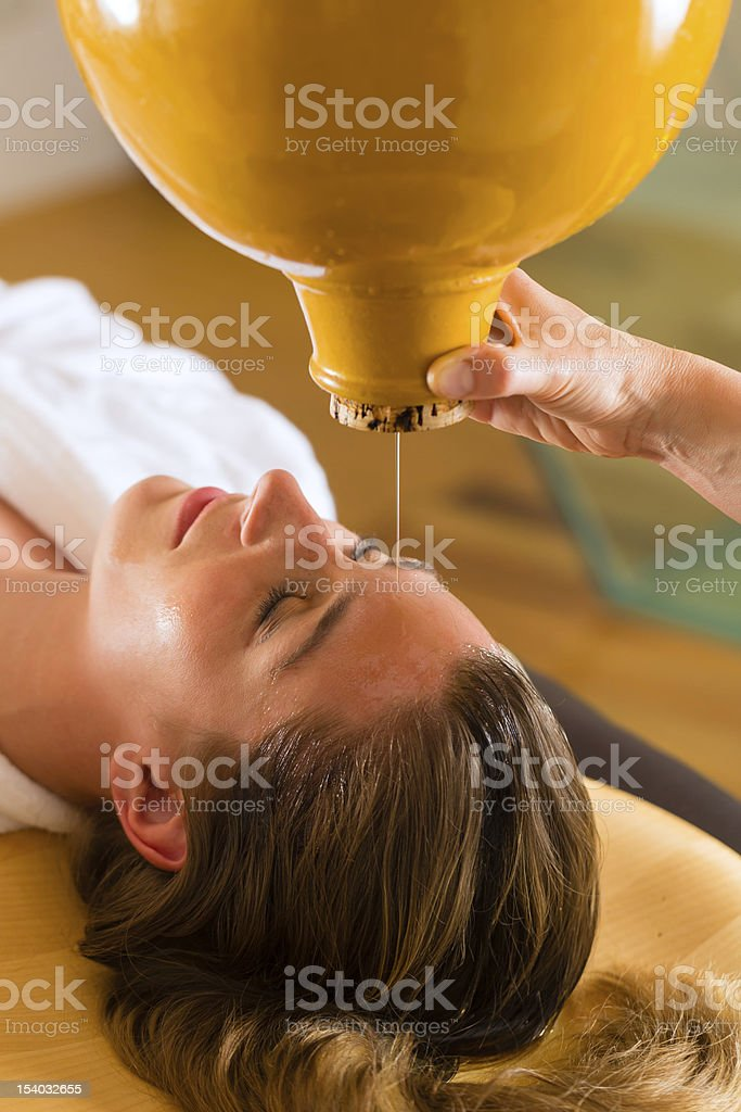 Woman enjoying a Ayurveda oil massage stock photo
