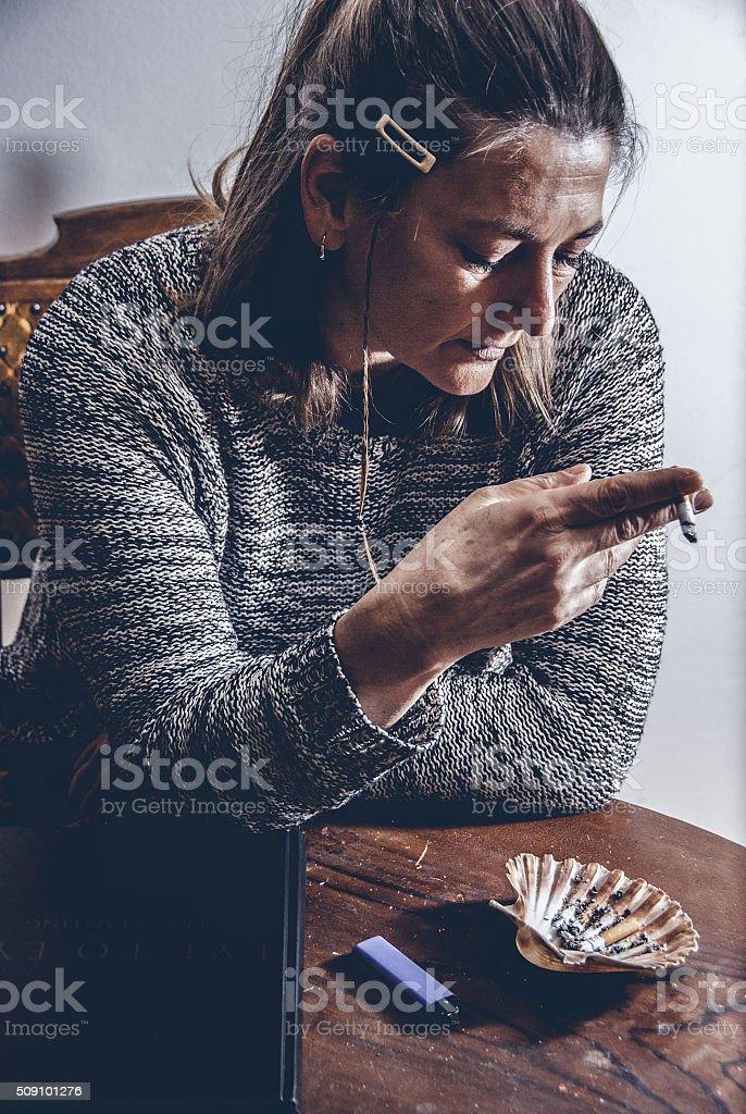 Woman Enjoying a Cigarette Indoors stock photo