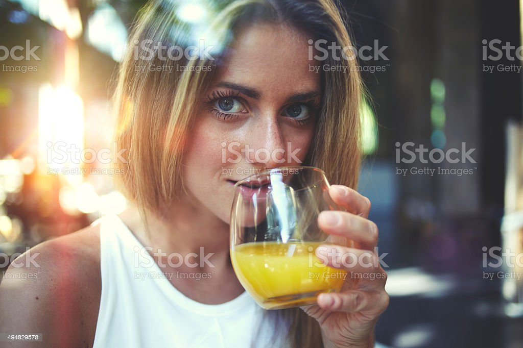Woman enjoying a natural fruit juice and looking at you stock photo