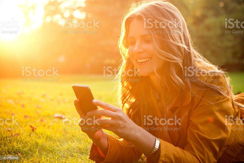 Woman enjoying autumn sun. stock photo